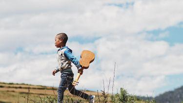 kind rent met een gitaar in zijn hand