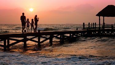 Moeder met haar gezin op een steiger aan zee, die vertelt over haar dagritme