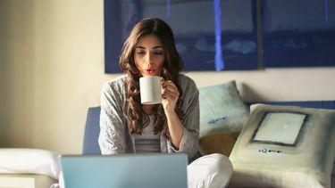 Vrouw zit bij thuiskomst op bed met laptop en kop thee