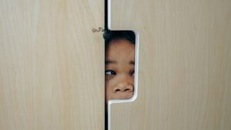 Kind dat verstoppertje speelt en in de kast zit