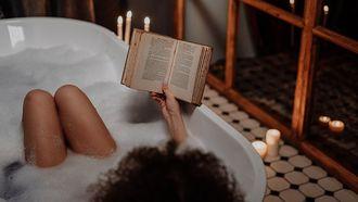 Vrouw die het beste weekend heeft en lekker een boek leest in bad