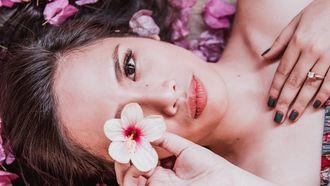 vrouw met bloem voor haar gezicht