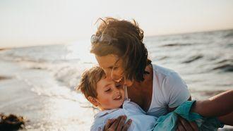Moeder met haar zoon op het strand en de opvoeding in Nederland doet