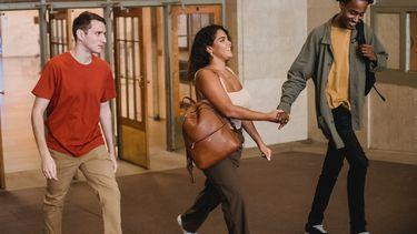 Vrouw houdt hand vast van een man, terwijl andere man jaloers kijkt. Verliefd op beste vriend van partner