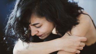 onbewuste stress / vrouw zit in elkaar gedoken op de grond