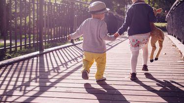 kinderen / broertje en zus lopen hand in hand