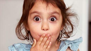 Meisje dat hand voor haar mond houdt nadat ze een gênant moment heeft veroorzaakt voor haar moeder