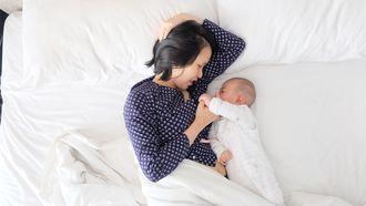 Moeder die samen met baby in bed slaapt