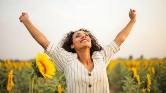 Vrouw heeft lachend haar armen in de lucht. Dit doen mentaal sterke mensen nooit
