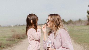 Moeder en dochter die snackje eten buiten