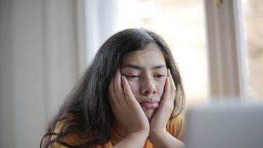 Vrouw leunt haar gezicht in handen en kijkt verveeld naar haar laptop, en heeft duidelijk last van een middagdip