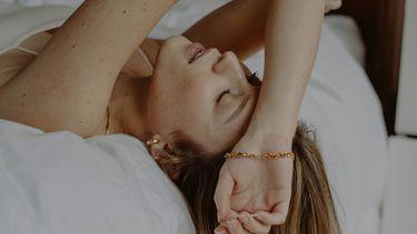 moeder ligt moe op bed met een mommy burn-out