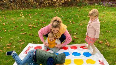 Laura die als millennial moeder met haar kinderen Twister speelt