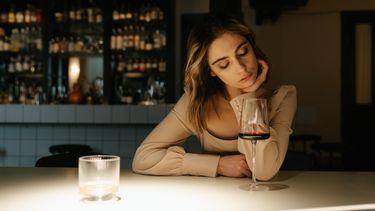 Vrouw die alleen aan de bar zit met een glas wijn en het heeft uitgemaakt met haar beste vriendin
