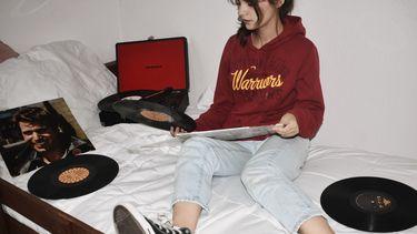 Meisje dat op bed zit met oude vinyl platen
