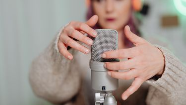 Vrouw beweegt haar nagels over een microfoon en doet ASMR