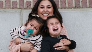 vrouw houdt kinderen vast maar kinderen willen niet meewerken