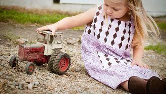 Kind met een rustig temperament dat aan het spelen is met een speelgoedauto