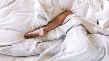 Vrouw die in bed ligt en opgewonden is