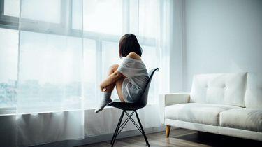 Vrouw die eenzaam uit het raam kijkt omdat ze geen vriendinnen heeft
