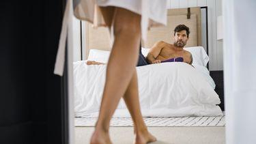 Vrouw die binnenkomt in kamer waar man op bed ligt met een sextoy
