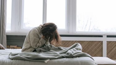 Vrouw zit verdrietig in een deken op bed en komt niet over haar ex heen