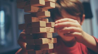 Een jongetje dat het spelletje Jenga speelt