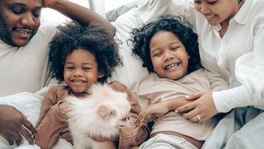 ouders liggen met kinderen in bed en zijn niet streng