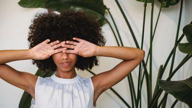 vrouw houdt twee handen voor haar gezicht alsof ze zich schaamt voor een taboe