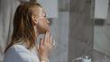 Vrouw die weet dat koffie goed is voor de huid en het als scrub op haar gezicht smeert