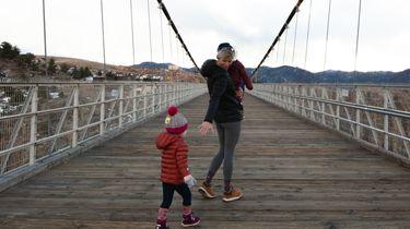 moederschap / moeder loopt met kinderen over een brug