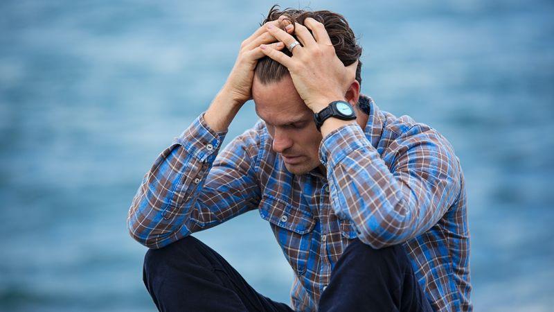 Man zit met handen in het haar. Platform voor mannen na miskraam