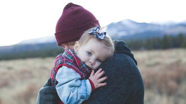 Vader die zijn dochter vasthoudt die veel te snel opgroeit en plots een dreumes is