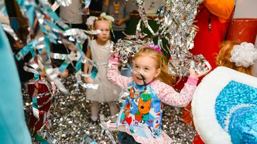Meisje op haar kinderfeestje dat springt en danst tussen de slingers