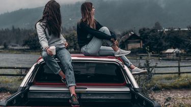 Twee vriendinnen op het dak van een auto die in een vriendschap zitten die niet meer werkt