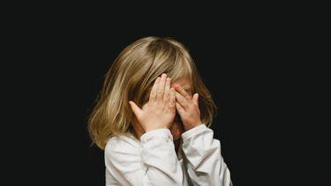 Verlegen kind / Kind met handen voor gezicht