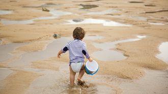 Peuter loopt op het strand om een emmertje water te halen