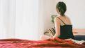 Vrouw die op de rand van haar bed zit nadat ze een mola-zwangerschap heeft gehad.