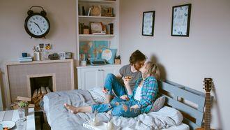 verliefd koppel op bed in een rommelige kamer