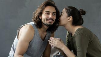 Vrouw fluistert iets in de oren van haar man, waarbij de stem bepalend is voor het karakter