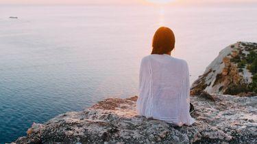 meisje aan de zee denkt aan negatieve ervaringen