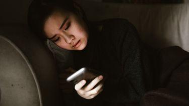 Vrouw ligt in het donker en kijkt op haar telefoon, waarschijnlijk moet ze aan haar ex denken