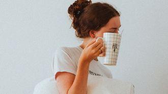 vrouw is vroeg opgestaan en loopt met kussen en koffie in de hand