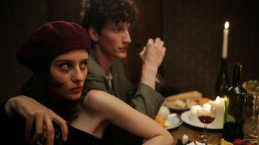 Frans koppel aan diner, terwijl de vrouw arrogant kijkt en wijnglas vast heeft. Slechte gewoonten van Parijse vrouwen.