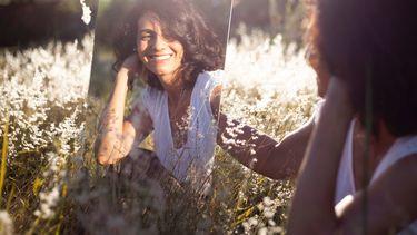 vrouw kijkt blij in de spiegel
