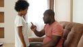 Vader die zijn zoon streng toespreekt in een harde opvoeding