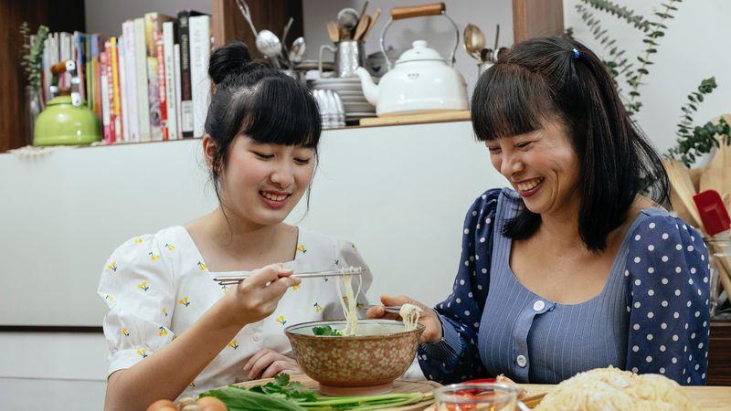 Twee Aziatische vrouwen eten soep met stokjes. Soep voor herstellen postpartum lichaam