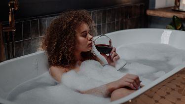 Vrouw in bad drinkt rode wijn. Verslaving