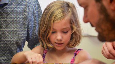 Kindje dat een puzzel legt met haar vader