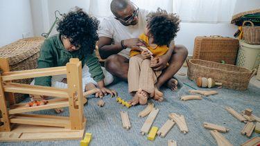 Kinderen aan het spelen met speelgoed en hun vader